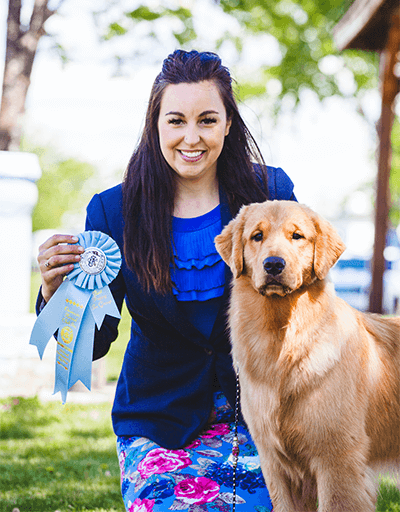 Picture of April proudly posing beside one of her show dog, a beautiful Golden Retriever, and holding its recently won show ribbon title in her right hand.